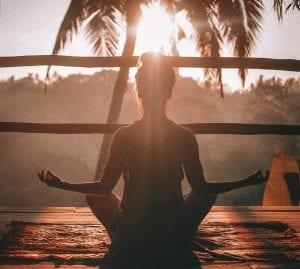 woman meditating on sunset