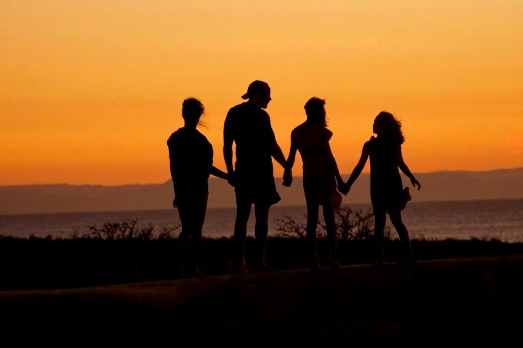 family holding hands during sunset